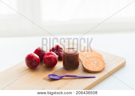 baby food, healthy eating and nutrition concept - fruit puree in glass jar with feeding spoon on wooden board
