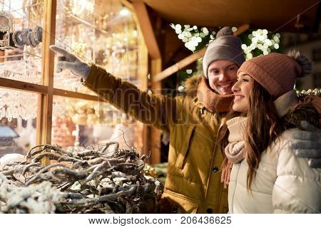 holidays, winter and people concept - happy couple at christmas market shop window in evening choosing souvenirs