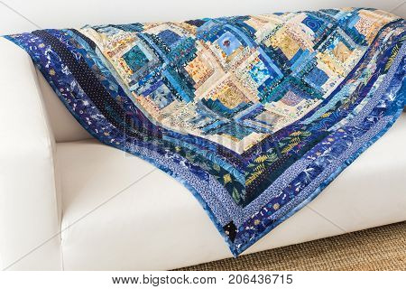 hobby, needlework, geometric, patchwork, interior, design concept - traditional blue and beige colored quilt created of patches with beautiful floral print covering minimalist white sofa