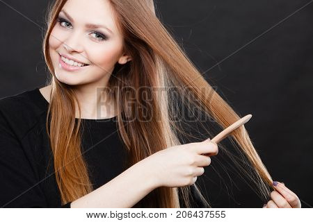 Healthy look concept. Girl combing brushing her hair by using wooden comb. Young woman taking care of everyday hygiene and natural beauty.