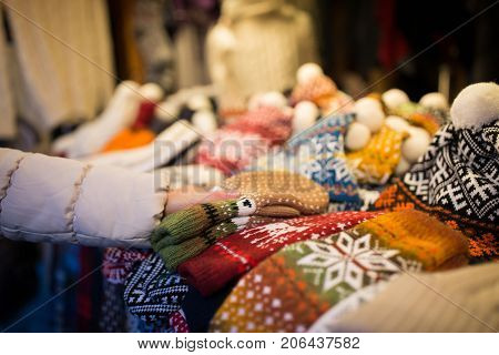 holidays and winter clothes concept - close up of woman buying woolen mittens at christmas market