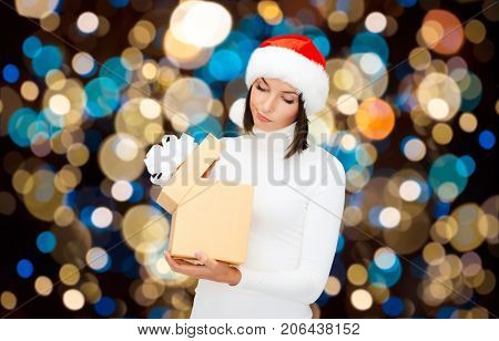 holidays, christmas and people concept - displeased woman in santa hat opening gift box over lights background