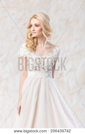 fashionable wedding dress, beautiful blonde model, bride hairstyle and makeup concept - splendid young woman in luxury white gown indoors on light background, lovely female posing in the studio