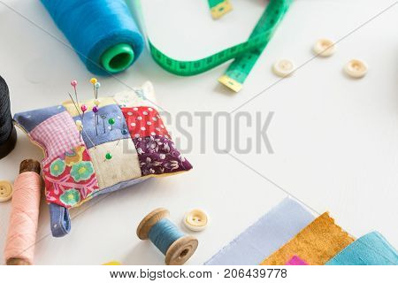 needlework, craft, sewing and tailoring concept - tools closeup on white desk, measuring meter, blue, pink and black thread spools , scraps of colorful fabric, pins and pincushion, white buttons