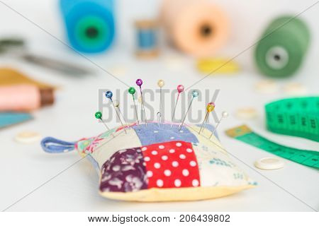 needlework, craft, sewing and tailoring concept - macro with white buttons, colorful stitched pincushion and beautiful pins, measuring meter, skeins of pink, blue and green thread, selective focus
