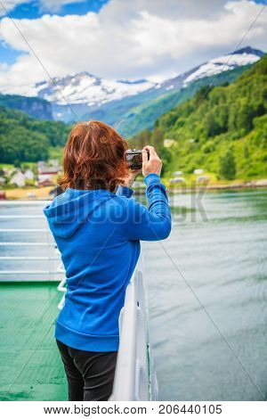 Tourism vacation and travel. Tourist woman on cruise ship enjoying fjord view taking photo with camera. Norway Scandinavia Europe. Norddalsfjorden as seen from ferry.
