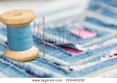 sewing and embroidery concept - installation of spool of blue threads and decorated with a blue textile with cut pattern, macro of stitching and designer decor in the form of labyrinth cut in fabric