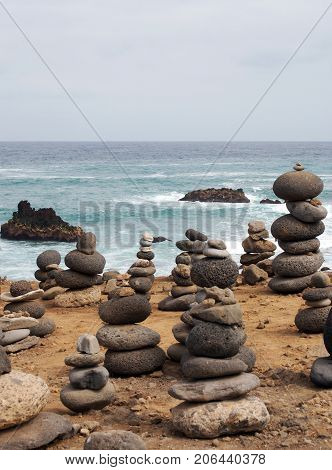 piles of stacked stones and pebbles in zen towers on a yellow sandy beach with sea breaking over rocks and blue calm sky