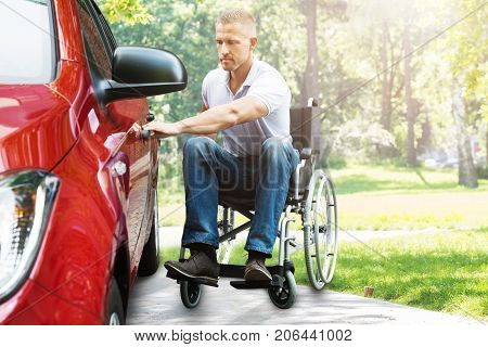 Young Man On Wheelchair Opening Red Car Door In The Park