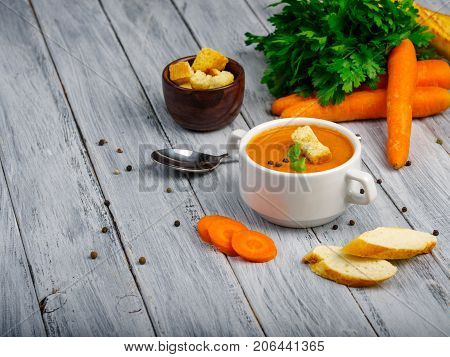 Curried carrot soup with cream fresh herbs and other vegetables on wooden grey table. Two piese of white bread big orange carrots. Close-up of plate with soup. Cope space. Food concept.