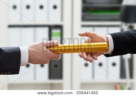 Close-up Of Businessman's Hand Passing Golden Relay Baton To His Colleague In Office