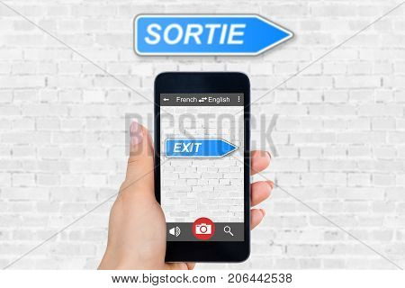 Person's Hand Holding Mobile Phone With Language Translator Application