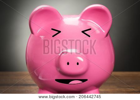 Photo Of Laughing Pink Piggybank On Wooden Table