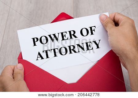 Close-up Of A Person's Hand Holding Power Of Attorney Document In Red Envelope