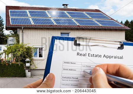 Close-up Of A Person's Hand Filling Real Estate Appraisal Form In Front Of House