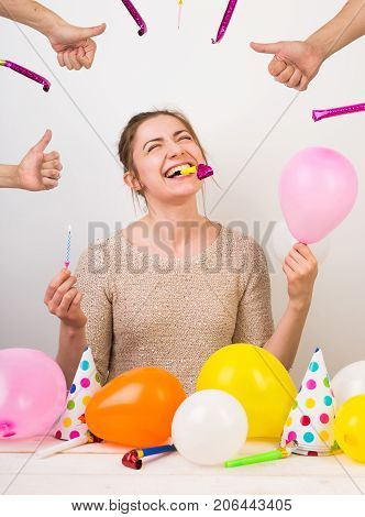 party, celebration, birthday concept. extremelly happy young girl is shrieking with laughter, holding small pink balloon in one arm, blue candle in other and birthday whistle with her teeth