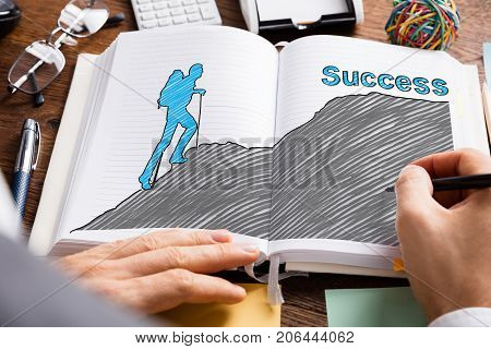 Close-up Of Businessperson Drawing Successful Career Concept In Book