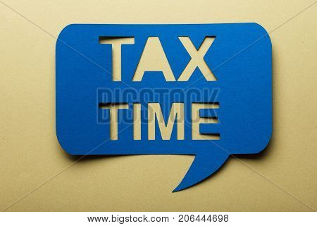 Blue Bubble Speech With Cut Out Text Tax Time On Brown Background