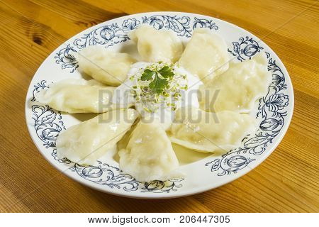 Boiled dumplings with cheese and creme fraiche on wooden table. Polish ukrainian russian traditional food.Fried dumplings with cheese and pork scratching on wooden table. Polish ukrainian russian traditional food.