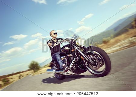 Guy riding a motorcycle on an open road