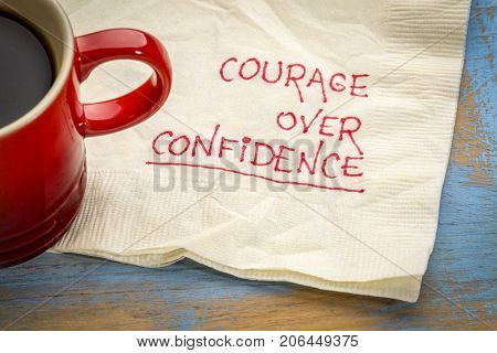 Courage over confidence doodle - handwriting on a napkin with cup of coffee