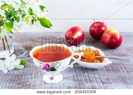 Cup of tea apple blossom and homemade apple jam on rustic wooden table. Breakfast tea with fruits and confiture.