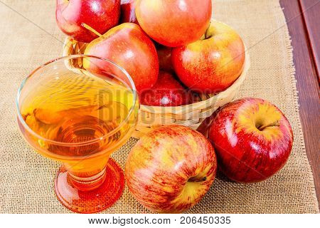 Apple cider glass and red apples in the rustic wicker basket on wooden background