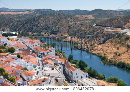 MERTOLA PORTUGAL - JUNE 30 2016: The view of Mertola city on the riverside of Guadiana with the bridge over the river on the background. Baixo Alentejo. Portugal