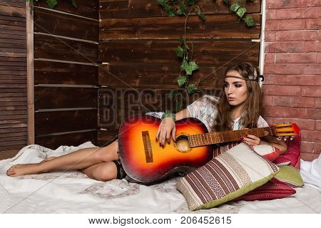 Cheerful young female hippie lies on a soft pillow and plays guitar on a wooden wall background.