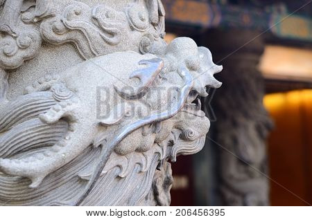The gabel end of an Asian designed building with a dragon statue