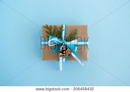Gift Box Wrapped Of Craft Paper, Blue And White Ribbons And Decorated Fir Branches And Pinecone On T