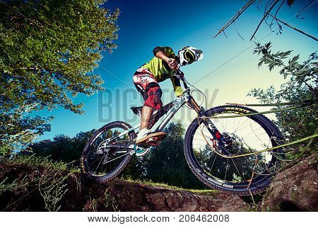 Mountain bike cyclist doing stunt on a mtb bike. Biker riding extreme sport bicycle. Cool athlete cyclist on a bike. MTB biking. Moscow Russia - August 31 2017