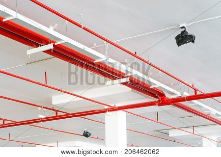 Fire sprinkler system with red pipes is placed to hanging from the ceiling inside of an unfinished new building.