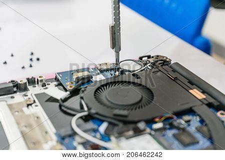 Repairman disassembling laptop motherboard. IT technician repairing broken laptop notebook computer. Electronic repair shop technology renovation business occupation concept