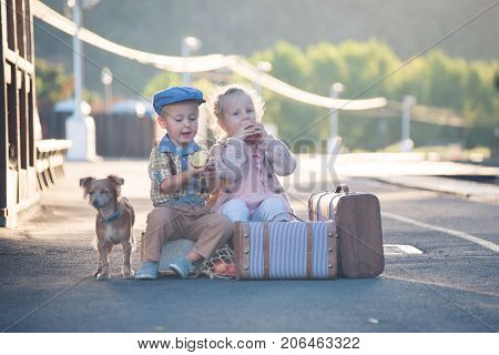 Small boy and girl eating apples outside, sitting on suitcases in vintage outfit, with dog nearby, waiting for a train on railroad station