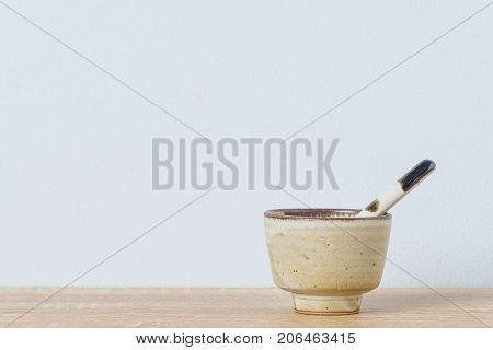 Ceramic Bowl And Ceramic Spoon On Wooden Table