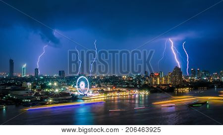 Thunder storm lightning strike on the dark cloudy sky over business building area in BangkokThailand. Bangkok is the capital of Thailand and also the most populated city. poster
