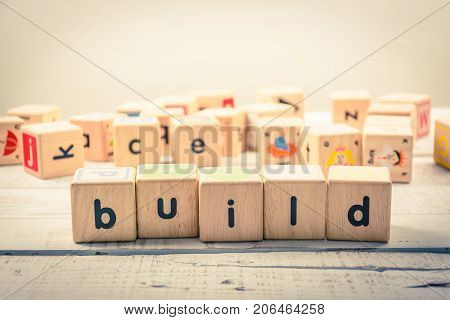 Word ' build ' wood Cubic on the wood
