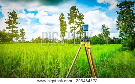 GPS surveying instrument install on tripod in green rice field Thailand