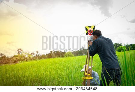 Asian smart engineer or surveyor in black jeans and long sleeve shirt are measuring the lands of rice field by Theodolite.