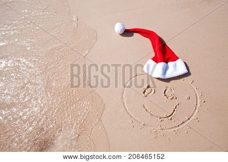 drawing of a happy face and red cap of santa on the sand of the red sea washing the wave