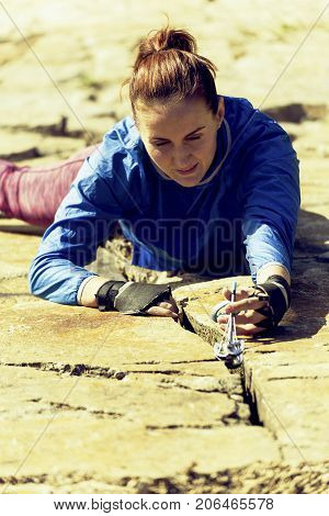woman rock climber climbs on the cliff. rock climber climbs on a rocky wall. woman makes hard move. top view