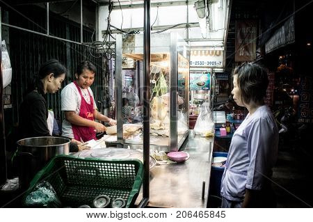 BANGKOK THAILAND - AUGUST 14: An unidentified customer waits next to the food stall as the two unidentified vendor prepares the food on the side of the road on August 14 2017 in Bangkok.