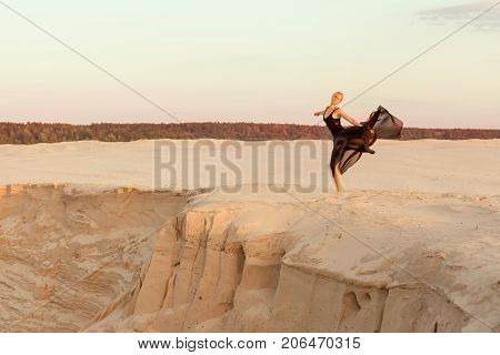 Female dancer performs on a sand dune she performs the performance.