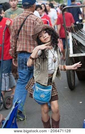 BANGKOK THAILAND - DECEMBER 22 2007 : The Chatuchak Weekend Market is the largest market in Thailand. A young girl sings and dances in the street
