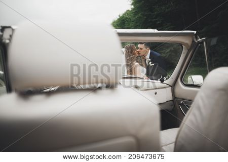 Just married couple in the luxury retro car on their wedding day.