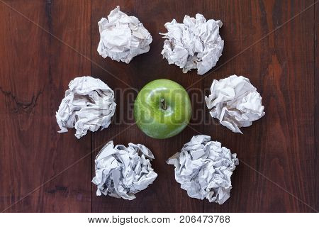 Green Apple And Crumpled Scraps Of Paper