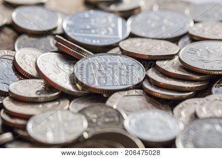 Low denomination five, ten and twenty pence coins in a pile. Selective focus - backgrounds