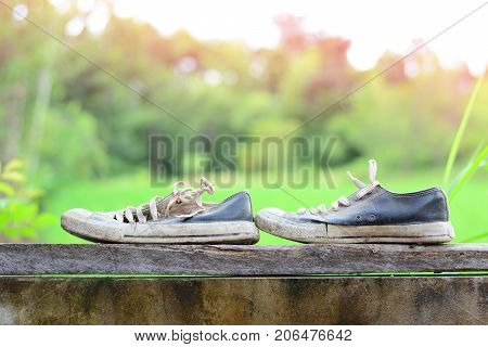 Old And Dirty Shoes  With Timber On Top Of Cement Wall