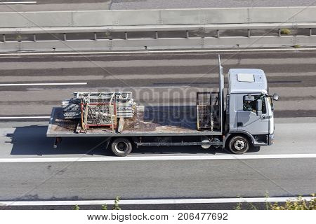 Flatbed truck loaded with scaffolds driving on the highway